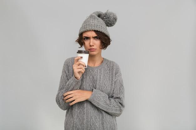 Smutna niezadowolona młoda kobieta pije kawę.