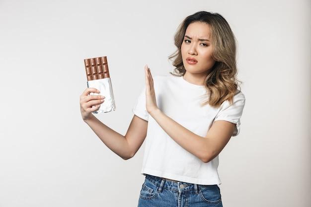 Smutna niezadowolona urocza młoda kobieta pozuje na białym tle nad białą ścianą trzymająca czekoladę zrobić gest zatrzymania