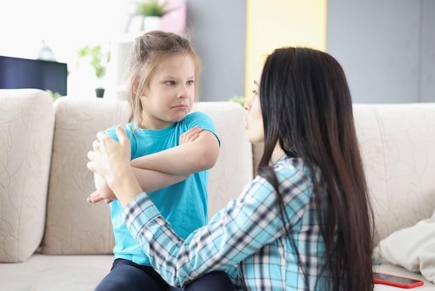 Smutna obrażona córka siedząca na kanapie odwracająca się do matki po kłótni w domu