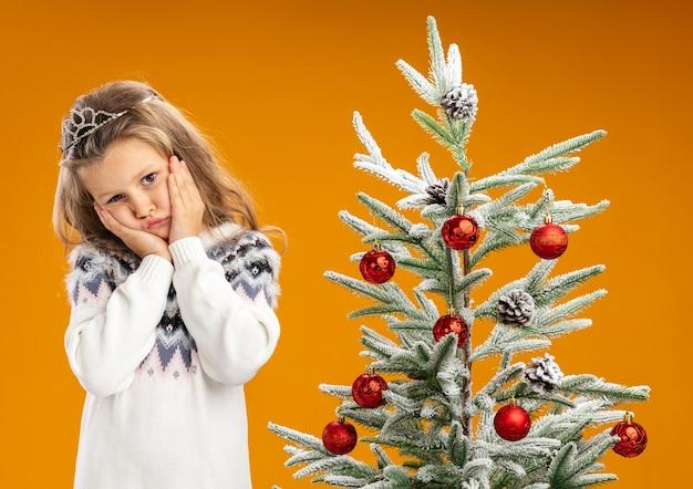 Smutna odchylana głowa mała dziewczynka stojąca w pobliżu choinki w diademie z girlandą na szyi kładąca ręce na policzkach odizolowana na pomarańczowym tle