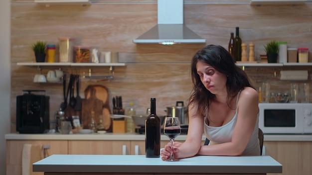 Smutna pani pije samotnie w kuchni. nieszczęśliwa osoba cierpiąca na migrenę, depresję, choroby i stany lękowe, wycieńczona z objawami zawrotów głowy, mająca problemy z alkoholizmem.