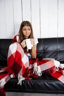 Smutna piękna kobieta ogląda tv, siedzi na kanapie w domu.