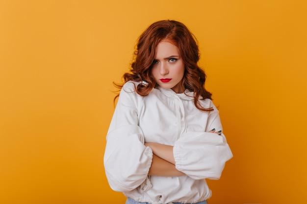 Smutna piękna kobieta ze stawianiem faliste rude włosy. kryty zdjęcie pięknej europejskiej pani na białym tle na żółtej ścianie.