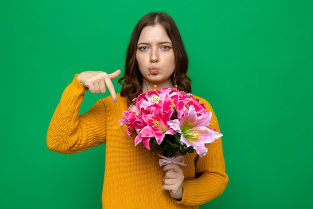 Smutna piękna młoda dziewczyna trzyma szczęśliwy dzień kobiety i wskazuje bukiet na zielonej ścianie