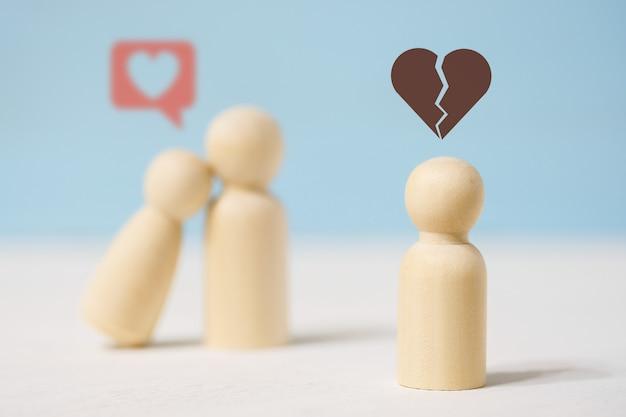 Smutna pojedyncza drewniana figura patrzy na zakochaną parę.