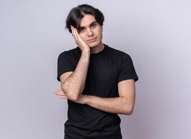 Smutna przechylająca się głowa młody przystojny facet ubrany w czarną koszulkę, kładąc rękę na policzku na białym tle na białej ścianie