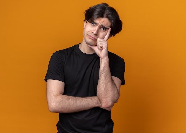 Smutna przechylająca się głowa młody przystojny facet ubrany w czarną koszulkę, kładąc rękę na policzku na białym tle na pomarańczowej ścianie