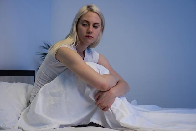 Smutna, przygnębiona kobieta siedząca w łóżku późno w nocy zamyślona i cierpiąca na bezsenność - image