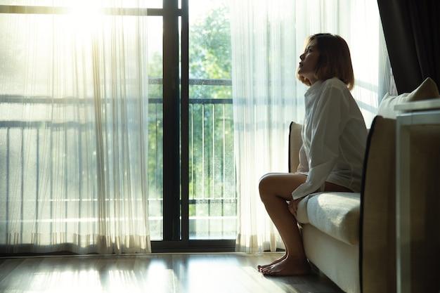 Smutna, przygnębiona nastolatka spędzająca czas samotnie w salonie, młoda zdenerwowana zamyślona kobieta czuje się samotna