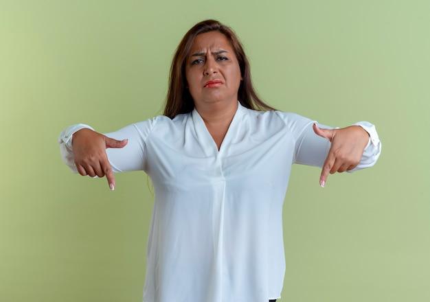 Smutna, przypadkowa kaukaski kobieta w średnim wieku wskazuje na dół na białym tle na oliwkowej ścianie
