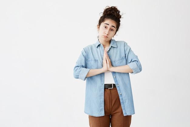 Smutna, religijna ciemnowłosa młoda kobieta trzymająca się za ręce w modlitwie w nadziei na szczęście. religia, pojęcie duchowości. smutna studencka dziewczyna w dżinsowej koszula błaga dla oceny