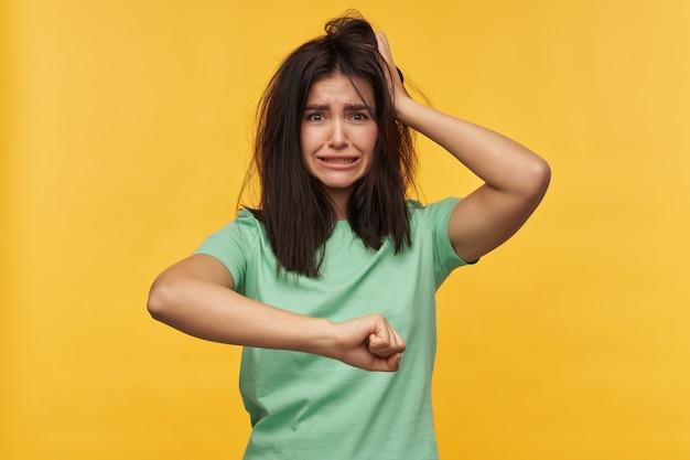 Smutna, rozczarowana młoda kobieta z ciemnymi rozczochranymi włosami w miętowej koszulce trzyma ręce na głowie i spóźnia się na pracę odizolowaną nad żółtą ścianą