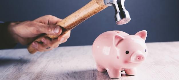 Smutna różowa skarbonka zaraz zostanie uderzona młotkiem w starym stylu vintage problem finansowy