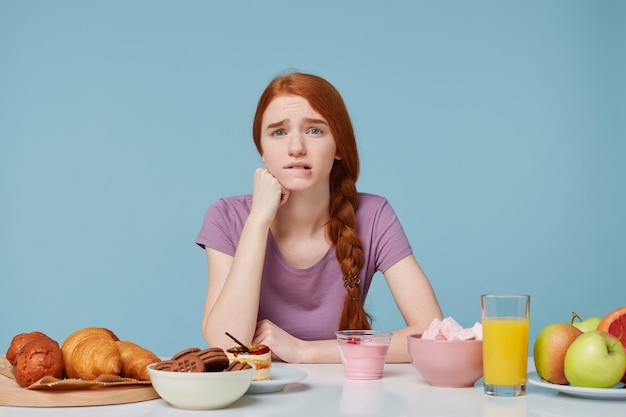 Smutna rudowłosa dziewczyna patrząc na kamerę przygryza wargę, martwi się wątpliwościami co do odżywiania, zdrowia, myśli o diecie