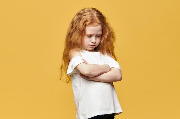Smutna rudowłosa dziewczyna ze skrzyżowanymi rękami