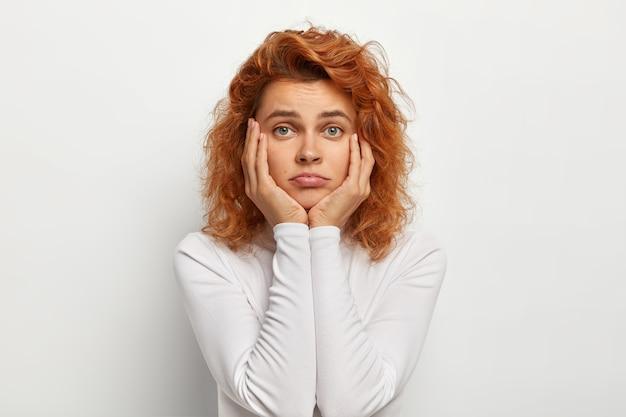 Smutna, samotna kobieta o falistych, lśniących włosach dotyka policzków