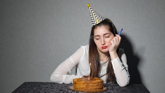 Smutna samotna kobieta w imprezowym kapeluszu świętująca urodziny sama, z bliska