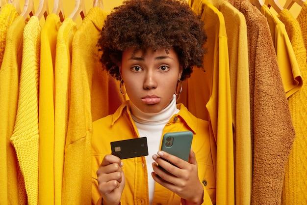 Smutna sfrustrowana afro kobieta dokonuje płatności przez portfel internetowy, trzyma kartę kredytową i nowoczesny telefon komórkowy