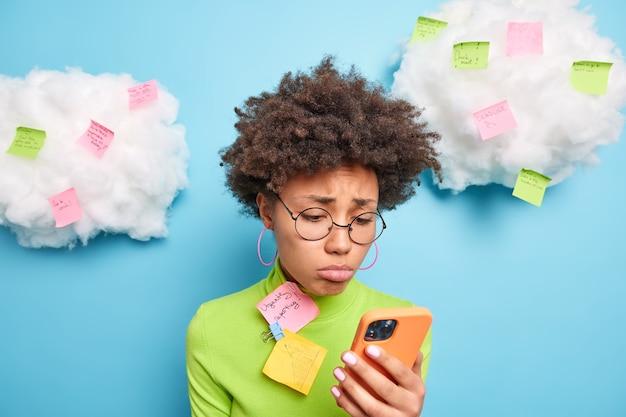 Smutna sfrustrowana afroamerykanka patrzy na smartfona sprawdza informacje robi notatki na naklejkach post it nosi okrągłe okulary zielony golf odizolowany na niebieskiej ścianie dzieli się pomysłami online