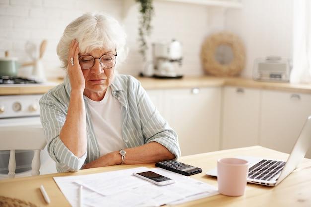 Smutna sfrustrowana emerytka o przygnębionym wyglądzie, trzymająca rękę na twarzy, obliczająca budżet rodzinny, siedząca przy kuchennym blacie z laptopem, papierami, kawą, kalkulatorem i telefonem komórkowym