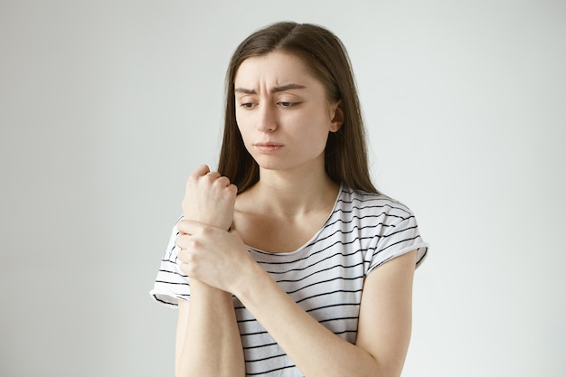Smutna, sfrustrowana młoda kobieta w pasiastym topie marszcząca brwi, trzymająca dłoń na obolałym nadgarstku, masująca obszar bólu, mająca bolesny wyraz twarzy, cierpiąca na bóle stawów, artretyzm lub dnę
