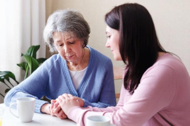 Smutna starsza kobieta jest pocieszana przez młodą kobietę i trzyma ją za rękę