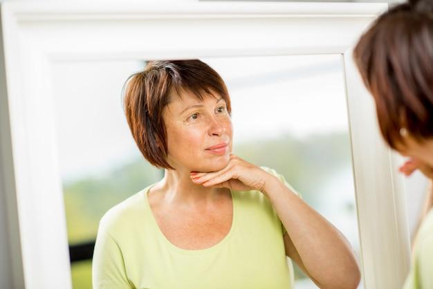 Smutna starsza kobieta patrząca na swoją twarz w lustro, martwiąca się zmarszczkami