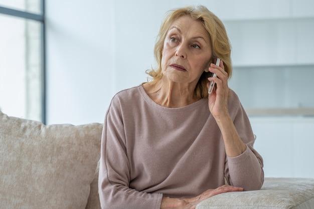 Smutna starsza kobieta rozmawia przez telefon komórkowy w domu siedząc na kanapie