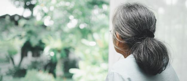 Smutna starsza kobieta używa walkera do stania przed oknami