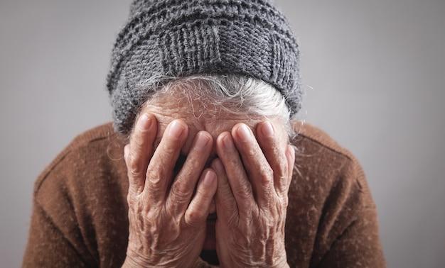 Smutna starsza kobieta zakrywająca twarz.