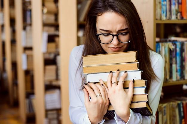 Smutna studentka brunetka w okularach trzyma stos książek, wygląda smutno i zmęczona nauką