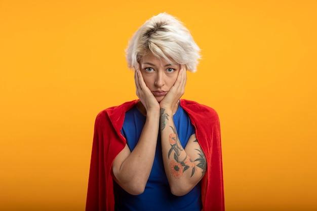 Smutna superwoman w czerwonej pelerynie kładzie ręce na twarzy odizolowanej na pomarańczowej ścianie