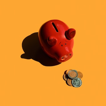 Smutna świnka-skarbonka patrzy na monety euro czerwona świnka-skarbonka z garścią monet minimalistyczna świnka na orange
