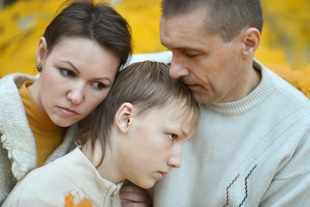 Smutna trzyosobowa rodzina na łonie natury