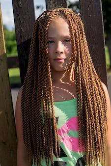 Smutna twarz nastolatka z długimi splecionymi włosami stojąca przy drewnianym płocie