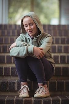 Smutna uczennica siedzi samotnie na schodach