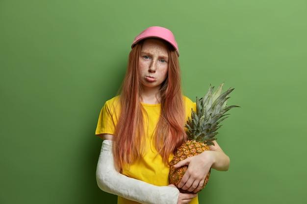 Smutna urażona piegowata ruda dziewczyna karana przez rodziców, trzyma soczystego ananasa, zaciska usta i wygląda ponuro, doznała traumy podczas ryzykownego sportu, pozuje przy zielonej ścianie.