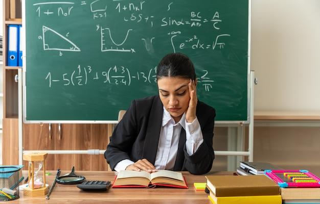 Smutna z opuszczoną głową młoda nauczycielka siedzi przy stole z przyborami szkolnymi, kładąc rękę na świątyni w klasie