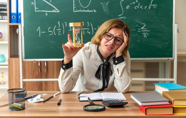 Smutna z zamkniętymi oczami młoda nauczycielka siedzi przy stole z przyborami szkolnymi trzymając klepsydrę w klasie
