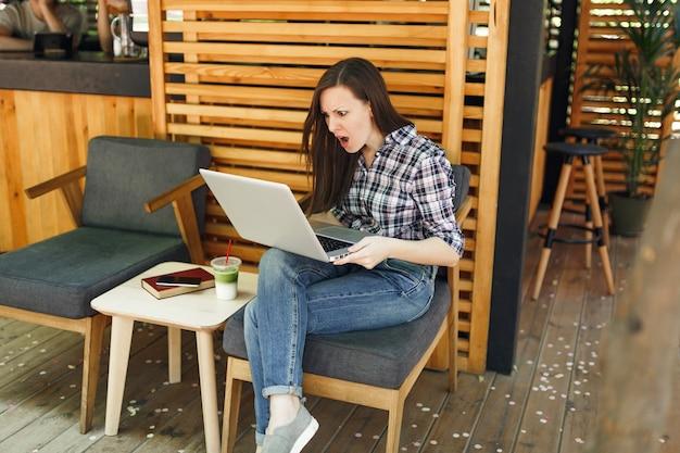 Smutna zdenerwowana krzycząca kobieta w plenerze na ulicy letnia kawiarnia siedząca w zwykłych ubraniach, pracująca na nowoczesnym komputerze typu laptop w czasie wolnym
