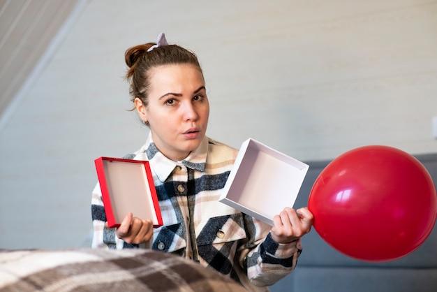 Smutna zdenerwowana młoda kobieta siedzi w domu, otwierając puste pudełko na prezent. sfrustrowana dziewczyna nie czuje