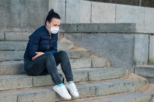 Smutna zdenerwowana przygnębiona dziewczyna, młoda samotna sfrustrowana kobieta siedząca na schodach, cierpiąca z powodu izolacji, koronawirusa. osoba w medycznych maski ochronne na twarzy. złamane serce, wirus, koncepcja epidemii