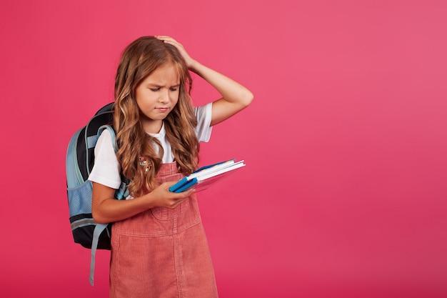 Smutna zdenerwowana uczennica dziewczyna z książkami w dłoniach. zdjęcie na różowym tle