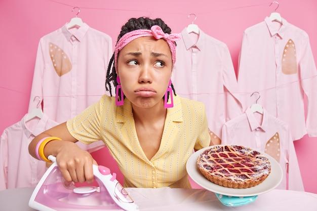 Smutna, zmartwiona ciemnoskóra kobieta z dredami trzyma upieczone ciasto na talerzu, używa żelazka elektrycznego do głaskania ubrań, czuje zmęczenie, nosi opaskę na głowie