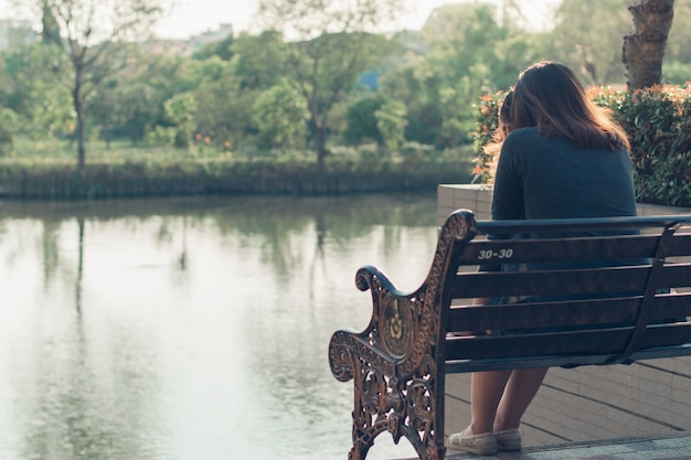 Smutna, zmartwiona i zmartwiona kobieta siedząca samotnie na zewnątrz