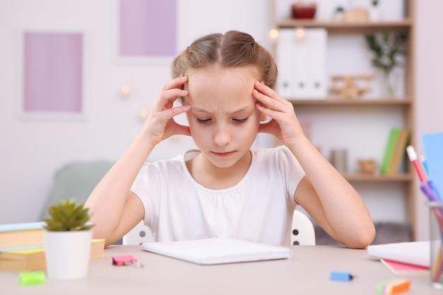 Smutna zmęczona dziewczyna odrabia lekcje we wnętrzu pokoju
