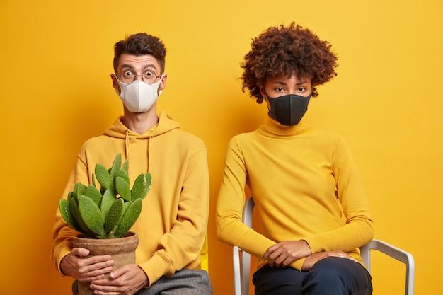 Smutna, znudzona kobieta i zszokowany facet siedzą razem na krzesłach w maskach medycznych i noszą doniczkowego kaktusa