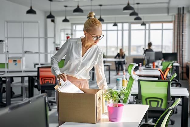 Smutna zwolniona pracownica zabiera swoje materiały biurowe z biura, pakuje się do pudełka. bezrobotna kobieta