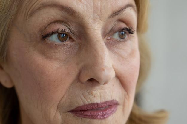 Smutne brązowe oczy starszej kobiety odwracającej wzrok zrobione zbliżenie