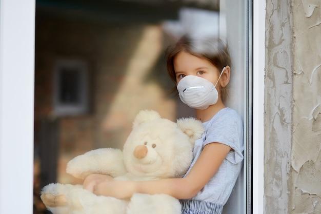 Smutne dziecko, mała dziewczynka w masce z misiem patrzącym z okna, kwarantanna koronawirusa